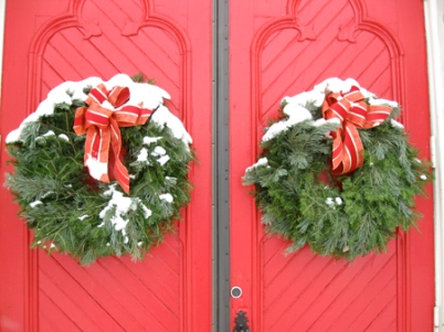 Beautiful Christmas wreaths decorating a church's doors.